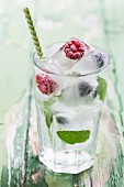 Ice cubes with berries and mint leaves in a glass of water with a straw on a green wooden table