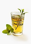 A glass of peppermint tea garnished with a sprig of mint