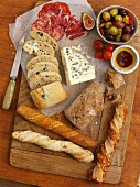 Various types of bread, blue cheese, salami, olives and olive oil