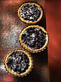 Three blueberry tartlets with sugar