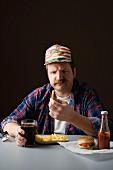 Typisch amerikanischer Mann schaut auf Pommes frites in seiner Hand