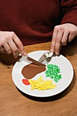 A man with a plate of steak, chips, peas and ketchup made from paper