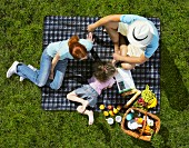 A family having a picnic on a blanket on the lawn