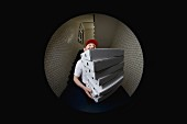 A pizza delivery man with a stack of pizza boxes seen though a spyhole