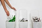 Hand stellt Glas in einen Recycling-Behälter