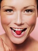 Frau hält eine Himbeere zwischen den Zähnen