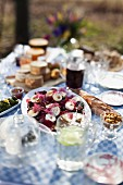 Goat's cheese with preserved pears, bread and olives on a garden table