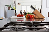Tomatoes, carrots, peppers and a knife block on a kitchen counter