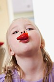 A blonde girl with a strawberry in her mouth