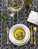Festive table setting with green glass star in bowl and gilt cutlery on black and white printed tablecloth
