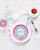 Hand-crafted table decorations with name printed on lace doily; set of plates, fork and teacup on white, shabby chic table