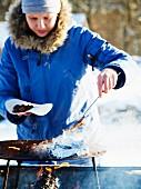 Frau grillt Wurst beim Winterpicknick