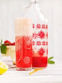 Homemade strawberry lemonade in a bottle and in a glass
