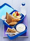 Toasted baked bean sandwiches, fruit salad, a muesli bar and yoghurt in a lunchbox