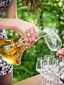 Frau giesst georgischen Kvevri-Weisswein zur Degustation aus Dekantierkaraffe in Gläser