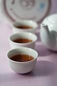 Aufgebrühter Pu-Ehr-Tee in weissen Teeschälchen