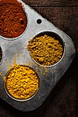 Turmeric, yellow curry and red curry powder in metal containers