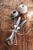 A bundle of knives and fork tied with kitchen twine