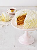 Hummingbird cake (mango and coconut cake with cream cheese), sliced on a cake stand