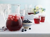 A jug of berry juice with ice cubes next to a bowl of blueberries