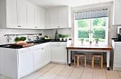 Eckelement einer schwedischen Landhausküche und Esstisch auf Rollen mit Klassiker-Hockern