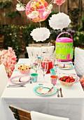 Mit bunt gemustertem Plastik- und Pappgeschirr gedeckter Partytisch im Garten