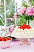 Strawberry cream cake on cake stand, bowl of strawberries and peonies on table in conservatory