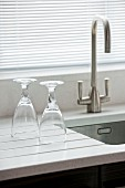 Two stemmed glasses on a polished quartz draining board (Silestone) next to a sink with a modern stainless steel tap