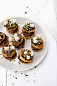 Mini profiteroles filled with chocolate cream and decorated with sweets and pistachio nuts