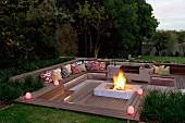 Abendstimmung über elegantem Sitzplatz im Garten, tiefer gelegte Holzterrasse mit integrierten und Sitzbänken, in der Mitte grosse Feuerstelle mit Feuer