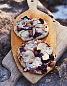 Mini pizzas topped with red cabbage, apple, cheese and bacon