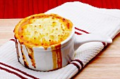 Fish pie in a ceramic pot on a tea towel