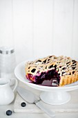 A sliced blueberry pie on a cake stand