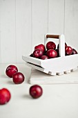 Red plums in white wooden basket and in front of it