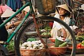 Female market stall holders at a vegetable market in Vietnam