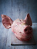 A pig's head on a chopping board against a wooden board
