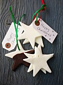 Star-shaped peppermint cream biscuits as gift tags on a wooden surface