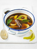 Pear compote in a spiced broth in an enamel bowl
