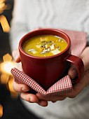 Hands holding a cup of spicy pumpkin soup