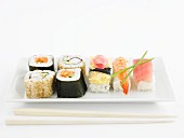 Various types of sushi on a rectangular porcelain plate