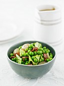 A green pea medley with bacon and shallots in a green bowl