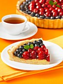 A slice of berry tart with a cup of tea