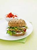 A grilled chicken burger on a wholemeal bun with lettuce and tomato