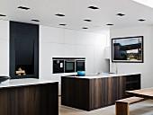 Elegante, monolithische Küchentheken mit Holzfront, vor weissen Einbauschränken, teilweise mit Einbaugeräte