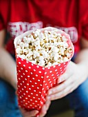 Popcorn in a red paper bag with white spots