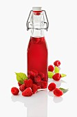 A bottle of raspberry vinegar and fresh raspberries