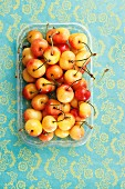 A punnet of yellow cherries seen from above
