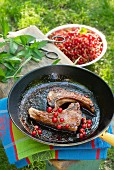 Two lamb chops with redcurrants in a frying pan on a garden table
