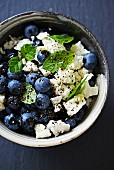 Blueberries with goat's cheese, mint leaves, pepper and olive oil