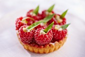 A raspberry tartlet topped with stuffed raspberries